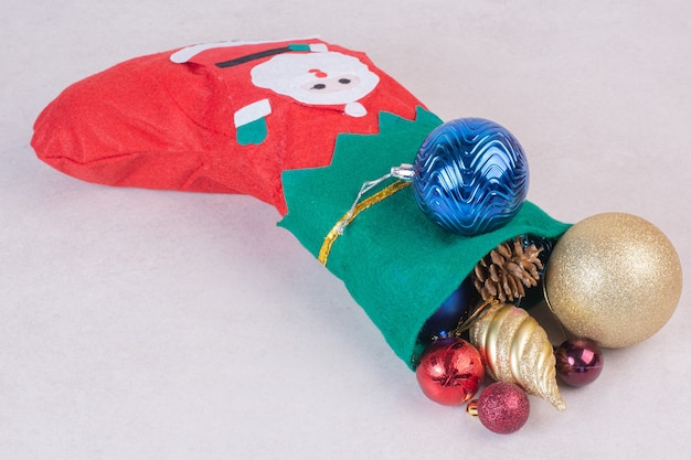 Christmas sock full of festive balls on white surface