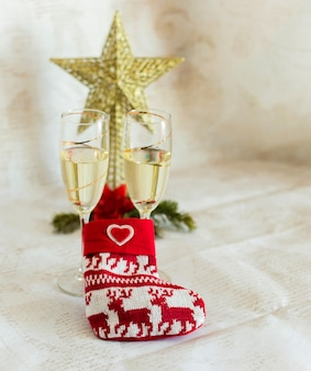 Christmas sock with glasses of champagne and golden star