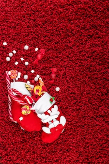 Christmas socks full of candy and sweets on red fleecy surface flat lay