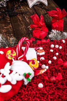 赤い羊毛の背景にキャンディーやお菓子でいっぱいのクリスマスソックス