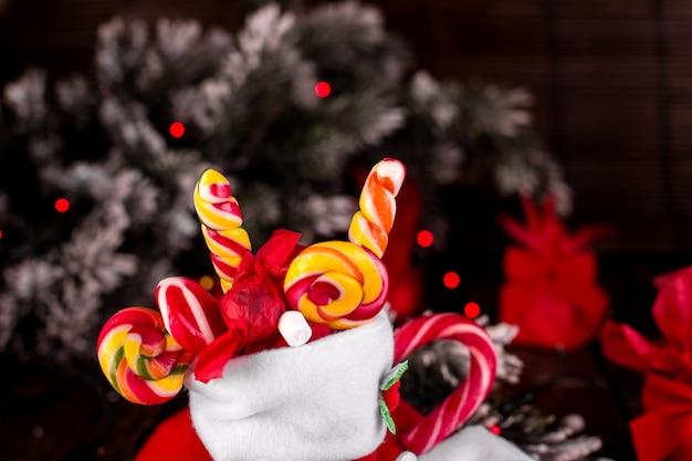 Рождественские носки, полные конфет и сладостей на деревянном фоне