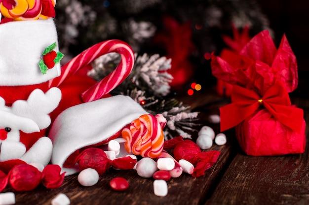 木製の背景にキャンディーやお菓子でいっぱいのクリスマスソックス