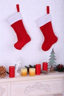 暖炉の上の壁に掛かっているクリスマスの靴下