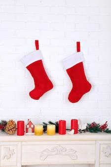 벽난로 위의 벽에 매달려 있는 크리스마스 양말