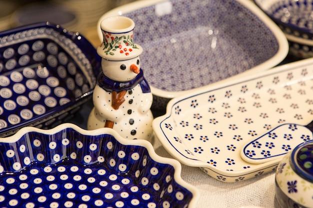 유럽의 카운터에 있는 크리스마스 기념품, 시장 카운터에 있는 유약을 바른 세라믹 요리.