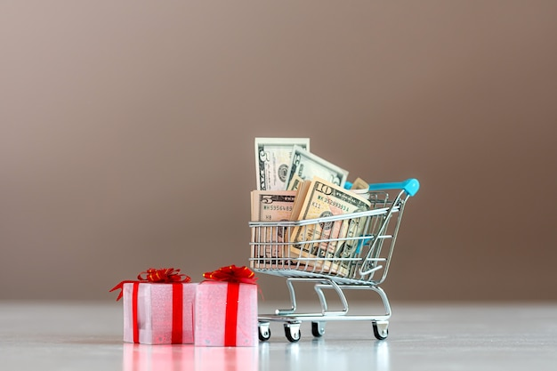 Christmas spending planning concept , gift boxes and shopping cart full of money