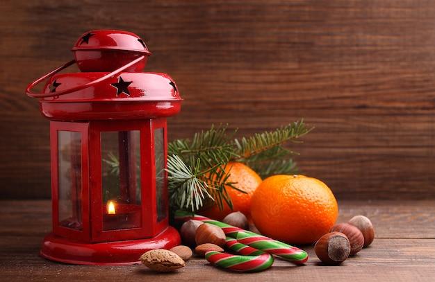 クリスマスの精神:ナッツ、みかん、クリスマスツリー、ナッツ、暗い背景の木の懐中電灯