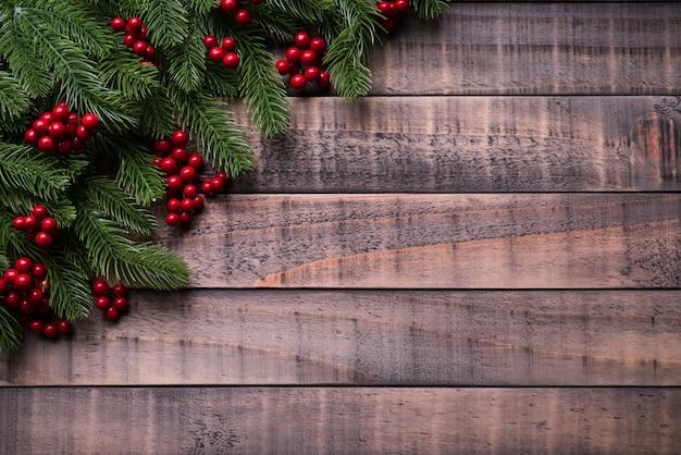 クリスマススプルースの枝、古い木製の背景に赤い果実。