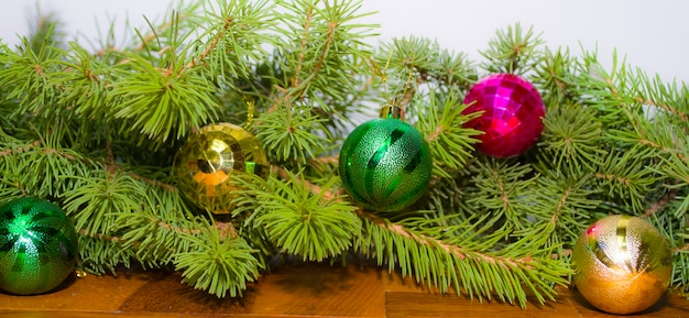 Рождественские еловые веточки и красивый блестящий шар, изолированные на белом фоне