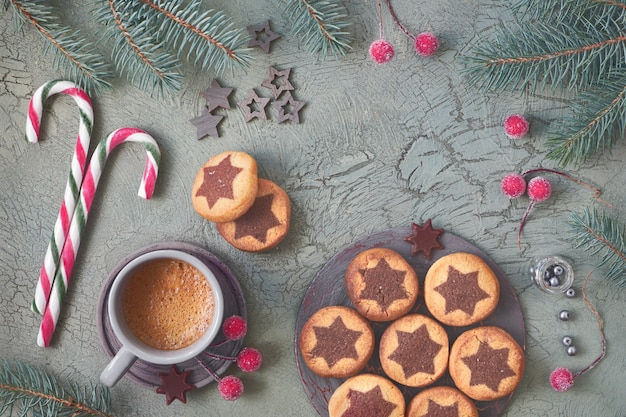 Christmas star cookies and coffee on rustic green background with fir twigs and xmas decorations