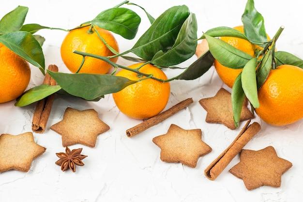 コピースペースと白い背景の上のスパイスとマンダリンとクリスマスの星のクッキー。上面図