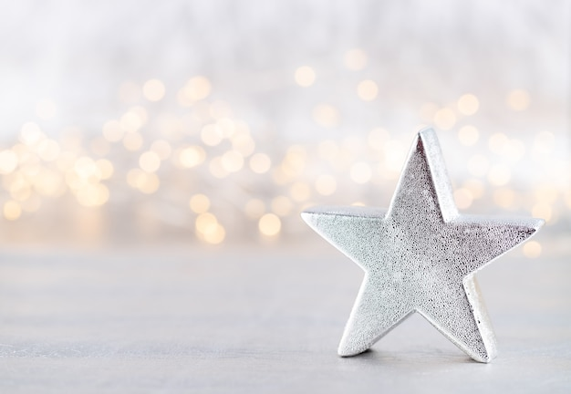 Christmas star, decor on bokeh silver background. christmas or new year minimal concept.