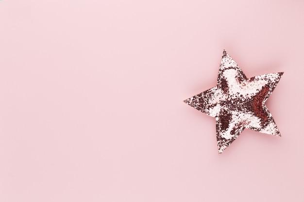 パステルカラーの背景にクリスマスの星の装飾クリスマスまたは新年の最小限のコンセプト