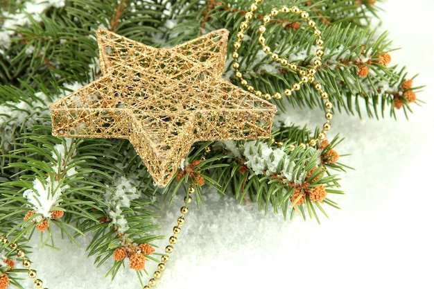 Christmas star on fir tree with snow, isolated on white