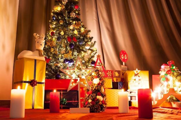 花輪と家の装飾が施されたクリスマスツリーの前のクリスマススター。装飾的でお祝いの緑の木
