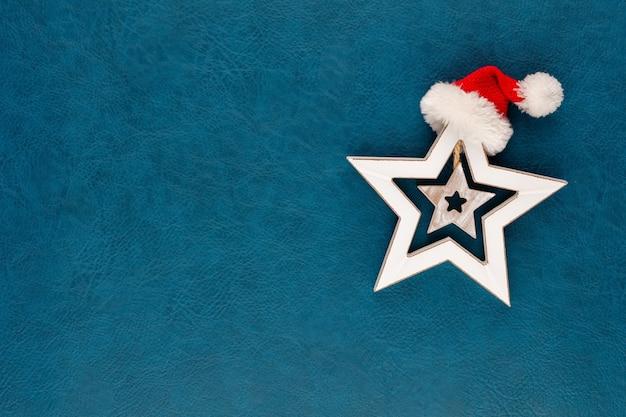 サンタ帽子の装飾が施されたクリスマススター。青い背景の上のクリスマスの星。