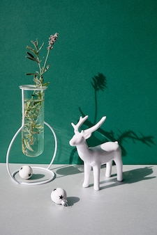 Christmas still life, minimal arrangement with winter flowers in modern glass vase and white xmas decor