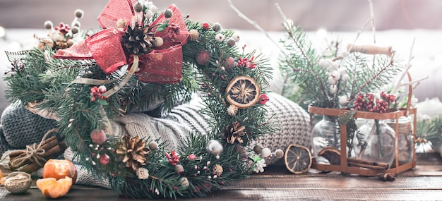 Рождественский натюрморт живой елки, украшения и праздничный венок на фоне вязаной одежды