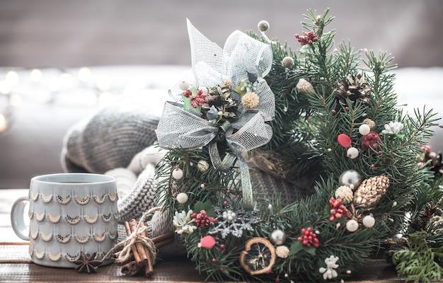 Рождественский натюрморт из елок и украшений, праздничный венок на фоне вязанной одежды и красивых чашек, рождественские специи