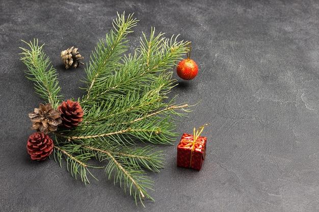 Рождественский натюрморт из еловых шишек, еловых веток и красных игрушек. черный фон. скопируйте пространство. вид сверху
