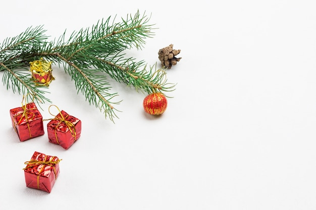 Рождественский натюрморт из еловых шишек, еловых веток и красных игрушек. белый фон. скопируйте пространство. вид сверху