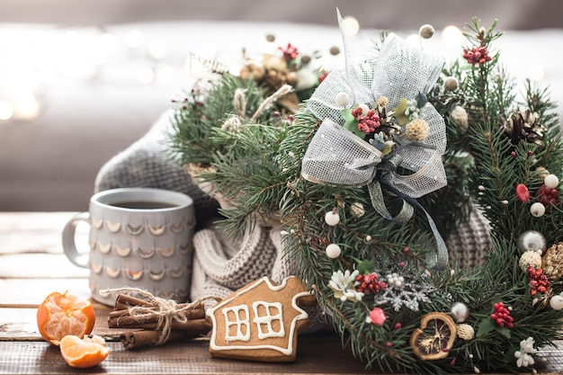 Christmas still life of trees and decorations, festive wreath on a table of knitted clothes and beautiful cups