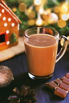 大きなガラスのコーヒーのマグカップ、ナッツの入ったチョコレート、ジンジャーブレッドの家、装飾品、ライトの付いたクリスマスツリーのあるクリスマスの静物画。お菓子や飲み物と居心地の良い家庭的な雰囲気のカード、クローズアップ