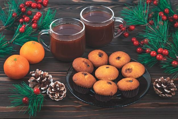 ホットココアドリンクとトウヒの枝、松ぼっくり、赤いヒイラギの果実とクリスマスの静物。ロマンチックな朝食のコンセプト、ダークウッドのテーブル、簡潔なデザイン。