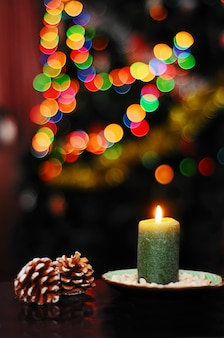 Christmas still life with pine cones and a green candle on a background of colored lights