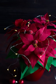 Christmas still life with poinsettia, gaultheria and decorations on wooden table