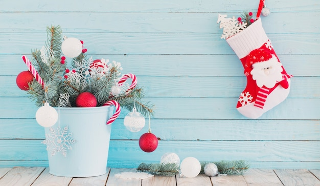 青い木製の背景に青いバケツのクリスマスの靴下とモミの枝