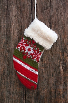 Christmas stocking hanging over rustic wooden background