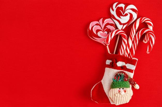 赤い背景の上のキャンディーとクリスマスの靴下