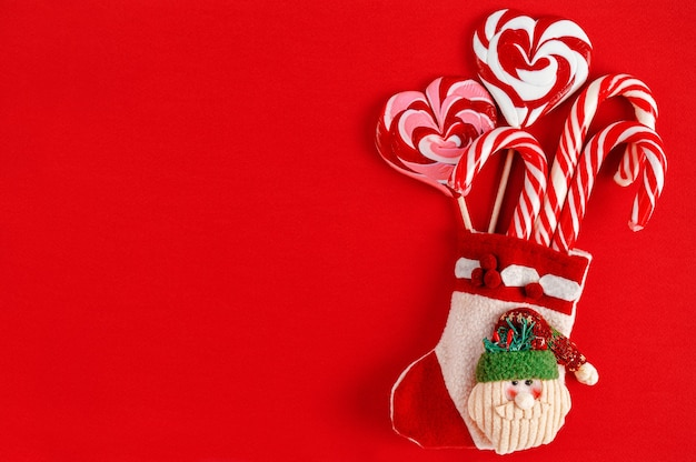 Christmas stocking with candies on red background