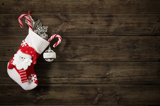Christmas stocking with gifts hanging on dark old wooden backgro