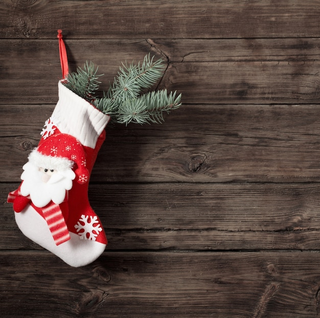 Christmas stocking with gifts hanging on dark old wooden wall