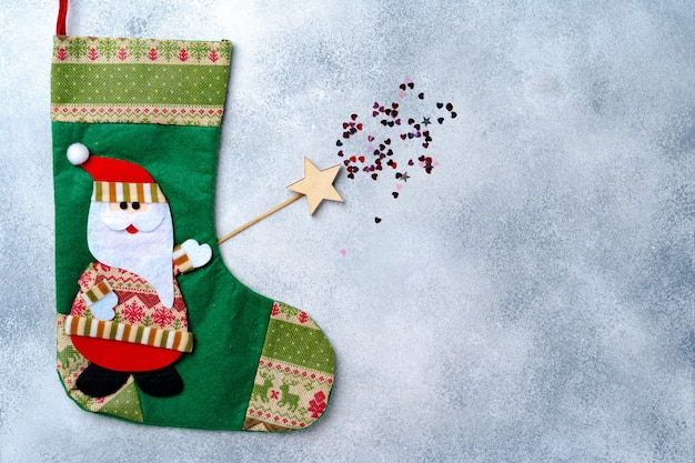 Christmas stocking with santa claus on grey background top view