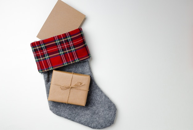 Christmas stocking with wrapped gift on white
