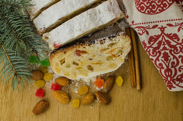 Christmas stollen on darkfestive background with fir twigs, lights and berries