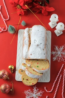 素朴な背景にクリスマスシュトーレン。ドイツの伝統的なクリスマスのお祝いペストリーデザート。クリスマスのためにシュトーレン。レッドコンセプトのクリスマステーマについて