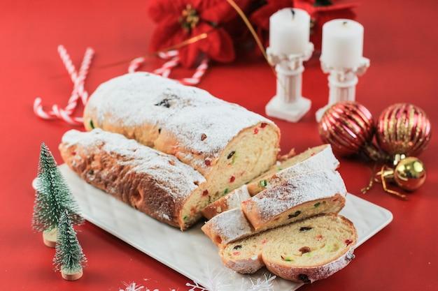 素朴な背景にクリスマスシュトーレン。ドイツの伝統的なクリスマスのお祝いペストリーデザート。クリスマスのためにシュトーレン、赤いコンセプト