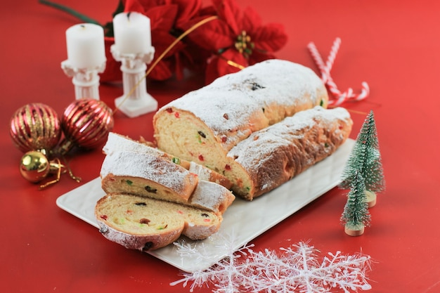 Christmas stollen on rustic background. traditional christmas festive pastry dessert from german. stollen for christmas, red concept
