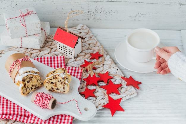 白い木製のテーブルでスライスされたクリスマスシュトーレン。クリスマスのためにシュトーレン。一杯のコーヒーを保持している暖かいセーターの女性の手
