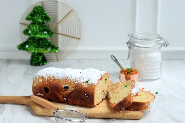 크리스마스 슈톨렌. 설탕을 입힌 전통적인 달콤한 과일 덩어리 독일 빵. 미니 트리 christmast 트리와 장식으로 장식 된 크리스마스 휴일 테이블 설정.