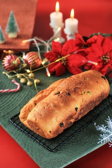 Christmas stollen. traditional sweet fruit loaf german bread with icing sugar. xmas holiday table setting, decorated with mini tree christmast tree and decoration.