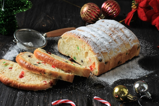 Christmas stollen. traditional sweet fruit loaf with icing sugar. xmas holiday table setting, decorated with mini tree christmast tree and decoration.