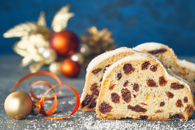 Christmas stollen on white-blue festive  with golden decorations