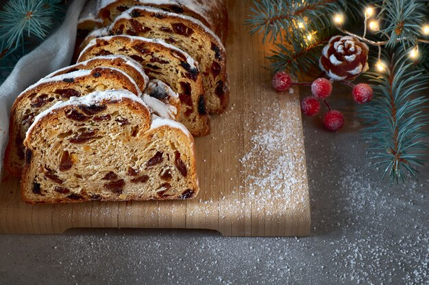 Christmas stollen with fir twigs, lights and and frosted berries