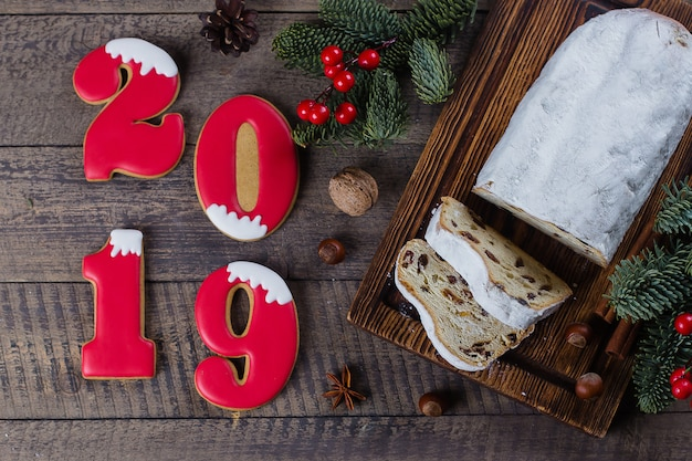 Christmas stollen on wooden background with number cookies 2019. traditional christmas pas
