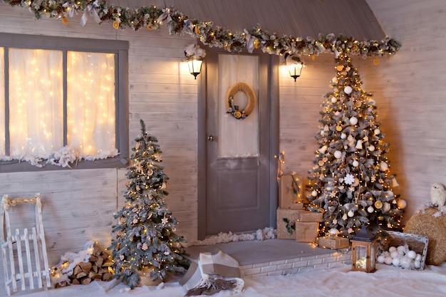 クリスマスツリーと花輪のクリスマススタイルの家。雪に覆われたクリスマスストリート。